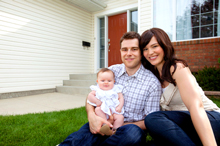 Family photo of Semper Fidelis Garage Doors clients in front of a home